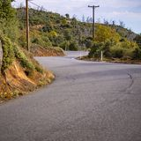 Winding paved road and power lines on a hill stock photos
