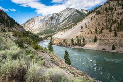 Winding River at the Bottom of a Canyon and Blue Sky with Clouds Royalty Free Stock Image
