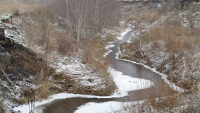 Winding river between hills covered with snow stock video
