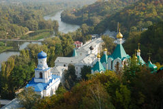 Winding river and religious buildings in the middle of forest, Ukraine. Meandering river Seversky Donets in the middle of green hills overgrown with forest and Royalty Free Stock Photos