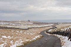 Winding road. Empty winding road in wintry country landscape Royalty Free Stock Photography