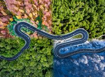 Winding road in all four seasons. Aerial view of a curved highway trough the forest. Composite drone roadway image. Winding road in all four seasons. Aerial view royalty free stock image