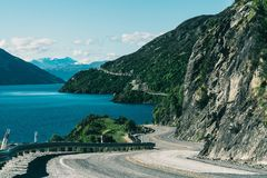 Winding road along mountain cliff and lake Stock Photo