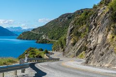Winding Road along Mountain Cliff and Lake. Landscape in Queenstown, New Zealand South Island. Travel and road trip in summer Royalty Free Stock Photography