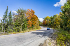 Winding Road in Autumn Lined with Fall Colour - Ontario, Canada. Blue Sports Car Traveling Down a Winding Road in Autumn Lined with Fall Colour - Ontario, Canada royalty free stock image