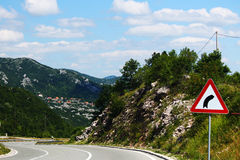 Winding road with curve sign in Montenegro. Beautiful wide winding road with curve sign in Montenegro, cliffs with vegetation on both sides and a small village Royalty Free Stock Photos