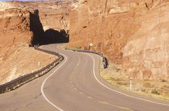 A winding road curves through red rock in the desert southwest USA Stock Photo