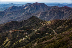 Winding road descends mountains in switchback pattern Stock Photos