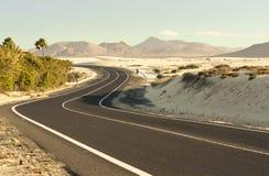 Winding Road in Desert. Winding road across the dunes of Corralejo, Fuerteventura, in the Canary Islands, Spain royalty free stock photos