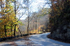 Winding road in the fall. A road winds through the trees on a clear fall day Stock Photography