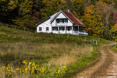 Winding Road and Farmhouse - Autumn / Fall - Vermont. A winding gravel road leads to a white painted farmhouse during a beautiful fall / autumn morning in Royalty Free Stock Photos