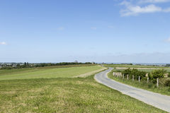 Winding road on a field Stock Photos