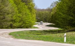 A winding road in the forest. A car and truck on a winding road in a forest stock photo
