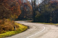 Winding road through the forest with red foliage. Beautiful autumn weather Royalty Free Stock Photography