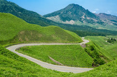 Winding road in a green highland Royalty Free Stock Photos