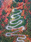 Winding road from high mountain pass, in autumn season, with orange forest stock image