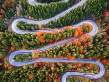 Winding road from high mountain pass, in autumn season, with orange forest stock photos