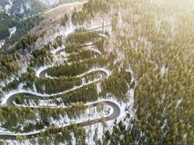 Winding road from high mountain pass, in winter time. Aerial view by drone Stock Images