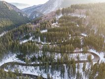 Winding road from high mountain pass, in winter time. Aerial view by drone Royalty Free Stock Images