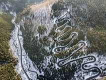 Winding road from high mountain pass, in winter time. Aerial view by drone Stock Photo