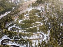 Winding road from high mountain pass, in winter time. Aerial view by drone Stock Photography