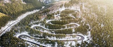 Winding road from high mountain pass, in winter time. Aerial view by drone Royalty Free Stock Photography