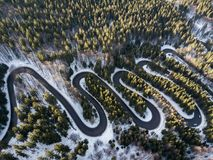 Winding road from high mountain pass, in winter time. Aerial view by drone. Romania Royalty Free Stock Images