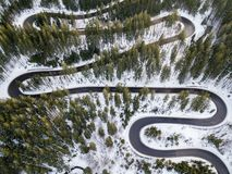 Winding road from high mountain pass, in winter time. Aerial view by drone Royalty Free Stock Photo