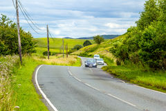 Winding road in the hills of Scotland with cars, sunny sumer day. Stock Photos