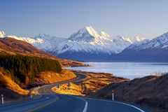 Winding road leading to Aoraki Mount Cook Village. During cold and clear sunrise in winter of 2016. The road flows along Lake Pukaki. This image was taken from Royalty Free Stock Images