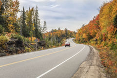 Winding Road Lined by Colorful Trees in Autumn Royalty Free Stock Photography