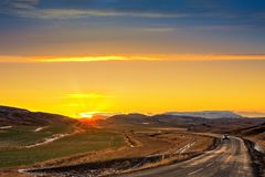 Winding road with lonely car. Crosses farm fields and mountains in rural Iceland at sunset stock photos