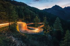 Winding road of Maloja Pass in Switzerland. The winding mountain road with light tracks from cars at the evening, Maloja Pass, Switzerland Royalty Free Stock Image