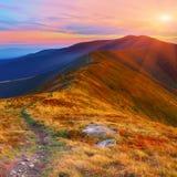 Winding road through meadows of  mountain range at sunset Stock Photo