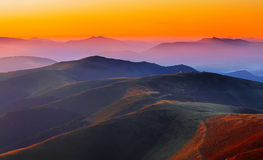 Winding road through meadows of  mountain range at sunset Royalty Free Stock Photos
