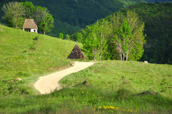 Winding road and a mountain hut Stock Photos