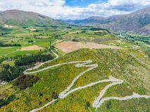 Winding Road on Mountain, Queenstown, New Zealand. Winding Road on Mountains near Queenstown, New Zealand from aerial view by drone flying over Crown Range Road stock photography