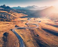 Winding road in mountain valley at sunset in autumn. Aerial view. Of asphalt road in Passo Giau. Dolomites, Italy. Top view of roadway, mountains, meadows with royalty free stock photos