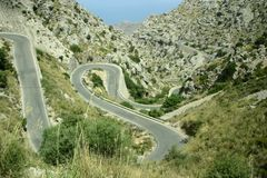 Winding road in mountains. Aerial view of winding road with hairpin bend in rocky mountains Stock Image