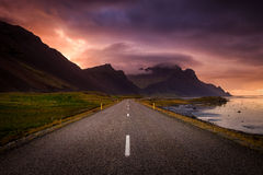 Winding road and mountains at dawn. Deserted winding road leading towards distant mountains. The mountains are shrouded in dark, stormy clouds broken by bright stock photography