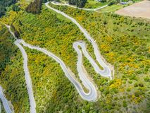 Winding road on mountain, Queenstown, New Zealand. Winding Road on Mountains near Queenstown, New Zealand from aerial view by drone flying over Crown Range Road Royalty Free Stock Photos