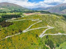 Winding Road on Mountain, Queenstown, New Zealand. Winding Road on Mountains near Queenstown, New Zealand from aerial view by drone flying over Crown Range Road stock image