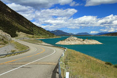 Winding Road Next to Mountain Lake Stock Photography