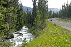 Winding road next to a mountain stream Stock Images