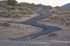 Winding road paved up a hill in Saratoga Springs. This is a temporary road created near a construction zone in Utah Valley stock photography
