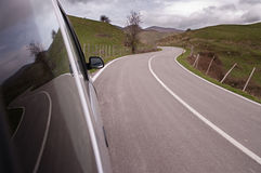 Winding road is reflected on side glass of a car Royalty Free Stock Photo