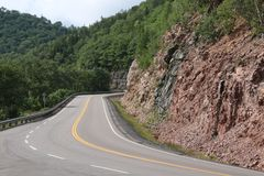 A winding road with a rock cliff on the right. And guardrails on the left, asphalt, beautiful, curve, green, highway, hill, landscape, mountain, mountains stock photography