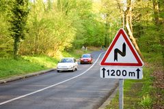 Winding road sign. With two cars in the background Royalty Free Stock Image