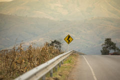 Winding Road Sign on asphalt road.  stock photo