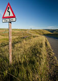 Winding road in countryside. Winding road sign in countryside with blue sky background Stock Image
